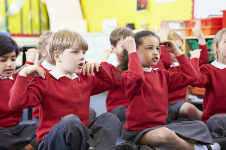 boy sitting: Pupils Perfoming Actions Whilst Singing Song