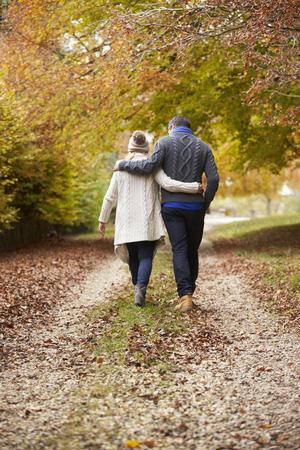 walking path: Rear View Of Couple Walking Along Autumn Path