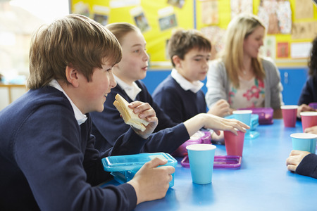 11 year old girl: Schoolchildren With Teacher Sitting At Table Eating Lunch Stock Photo