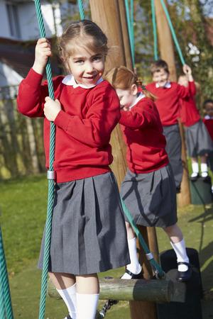 children clothing: Portrait Of Elementary School Pupils On Climbing Equipment Stock Photo