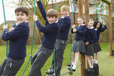 school year: Portrait Of Elementary School Pupils On Climbing Equipment Stock Photo