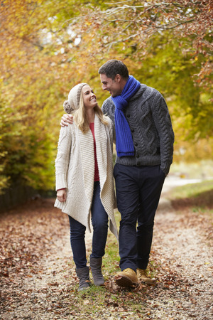 walking path: Couple Walking Along Autumn Path Stock Photo