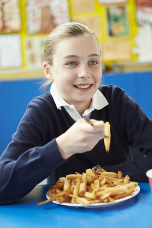 elementary schools: Female Pupil Eating Unhealthy School Lunch Stock Photo