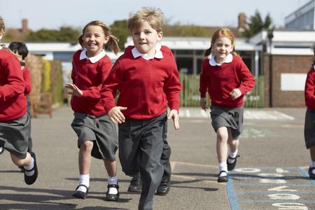 uniformes: Los alumnos de la escuela primaria que se ejecutan en patio