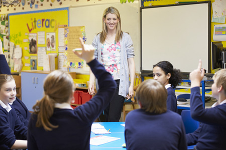 pupils: Teacher Teaching Lesson To Elementary School Pupils