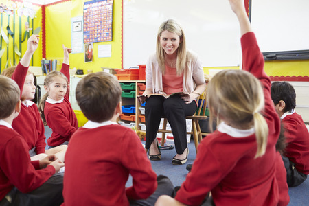 Teacher Reading Story To Elementary School Pupils