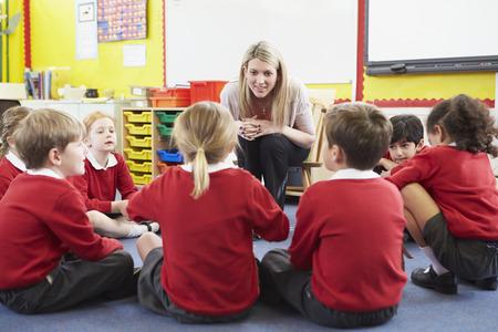 Elementary School Pupils Telling Story To Teacher