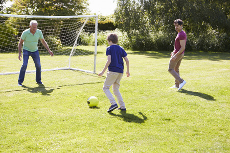 family playing: Male Three Generation Family Playing Football Together Stock Photo