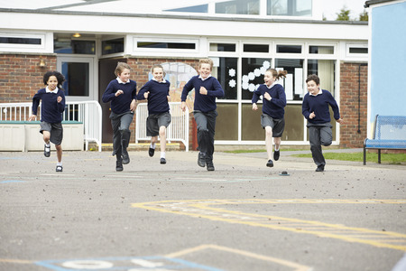 school uniforms: Group Of Elementary School Pupils Running In Playground