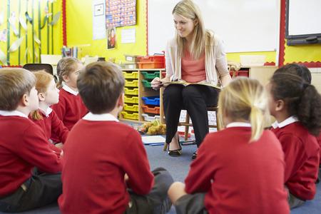 pupils: Teacher Reading Story To Elementary School Pupils