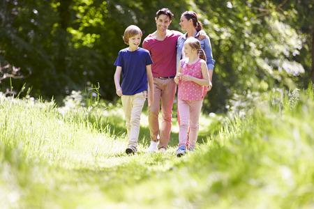 ni�os caminando: Familia que recorre a trav�s de campo del verano