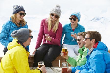 tomando alcohol: Grupo de amigos que disfrutan de la bebida en bar En la estación de esquí
