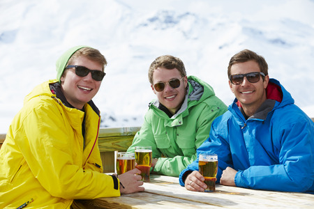 skiing: Group Of Young Men Enjoying Drink In Bar At Ski Resort