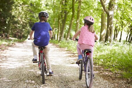 11 year old girl: Rear View Of Two Children On Cycle Ride In Countryside