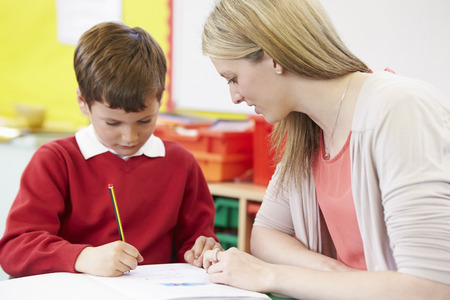 Teacher Helping Male Pupil With Practising Writing At Desk Stok Fotoğraf