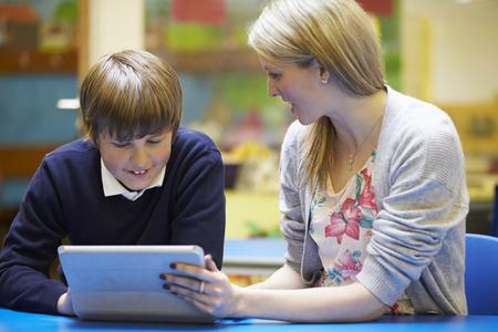 uniform: Profesor Con Pupila masculina que usa la tablilla digital en el aula