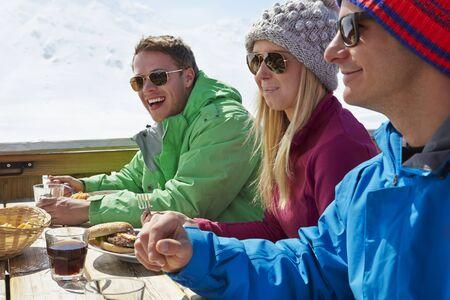 ski resort: Group Of Friends Enjoying Meal In Cafe At Ski Resort