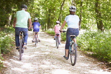 Grandparents With Grandchildren Cycling In Countryside Banco de Imagens
