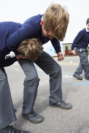 pelea: Dos muchachos que luchan en patio de la escuela