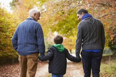 パス上を歩く男性セルオート世代家族の後姿 写真素材