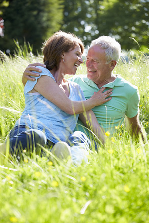 romantic couple: Senior Couple Relaxing In Summer Field Together Stock Photo