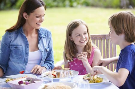 11 year old: Mother And Children Enjoying Outdoor Meal Together