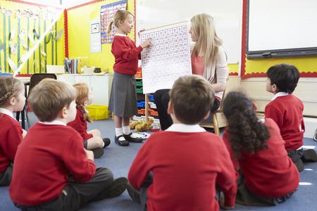 niños sentados: Profesor de Enseñanza de Matemáticas a los alumnos de Escuelas Primarias Foto de archivo