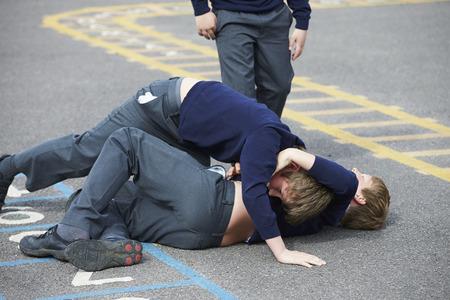 personas discutiendo: Dos muchachos que luchan en patio de la escuela