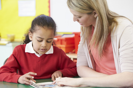 school year: Teacher Helping Female Pupil With Practising Reading At Desk