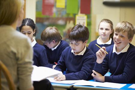 school uniform: Teacher Teaching Lesson To Elementary School Pupils