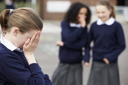 Female Elementary School Pupils Whispering In Playground Stock Photo