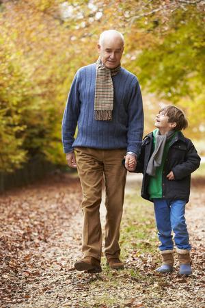 caminando: Abuelo y nieto que recorren a lo largo Camino Otoño
