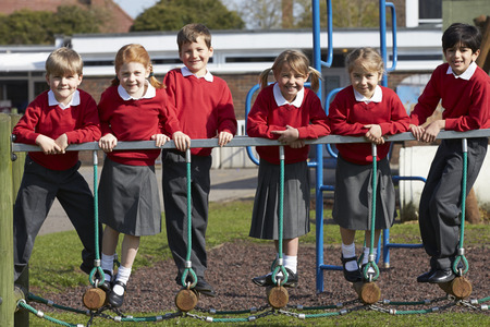 school uniforms: Portrait Of Elementary School Pupils On Climbing Equipment Stock Photo