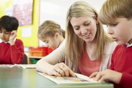 maestro: Profesor de ayuda a la pupila masculina con la lectura en el escritorio