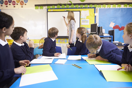 11 year old girl: Pupils Sitting At Table As Teacher Stands By Whiteboard