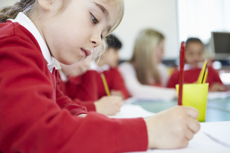 Female Elementary Pupil Working At Desk Standard-Bild
