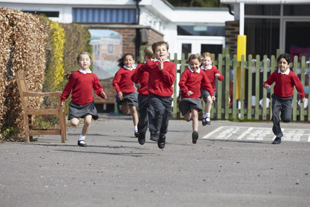 school year: Elementary School Pupils Running In Playground