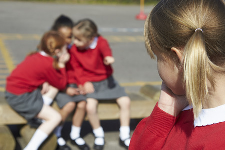 school uniforms: Female Elementary School Pupils Whispering In Playground Stock Photo
