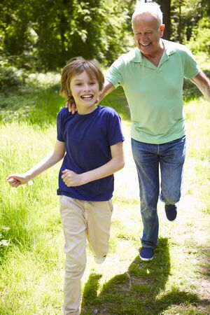grandkid: Grandfather With Grandson Running Through Countryside Stock Photo
