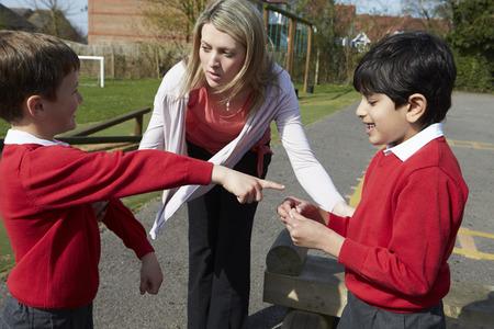 교사는 놀이터에서 싸우는 두 소년 중지