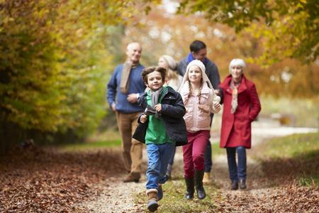 семья: Multl поколения семьи, прогулка вдоль осень Путь