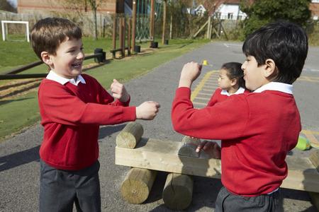 school playground: Two Boys Fighting In School Playground Stock Photo
