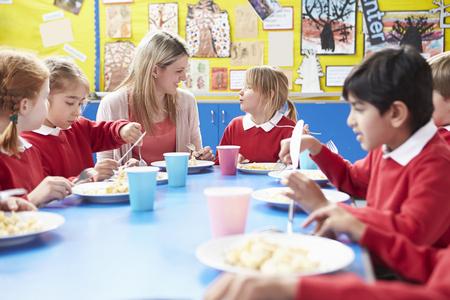 niños comiendo: Los escolares con el maestro sentado en la mesa de comer el almuerzo Foto de archivo