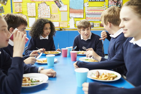school uniforms: Schoolchildren Sitting At Table Eating Cooked Lunch Stock Photo