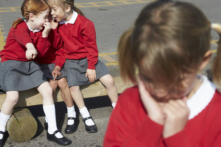 school year: Female Elementary School Pupils Whispering In Playground Stock Photo