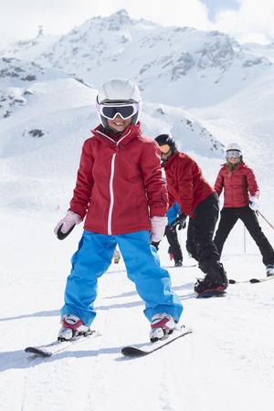 to ski: Family On Ski Holiday In Mountains