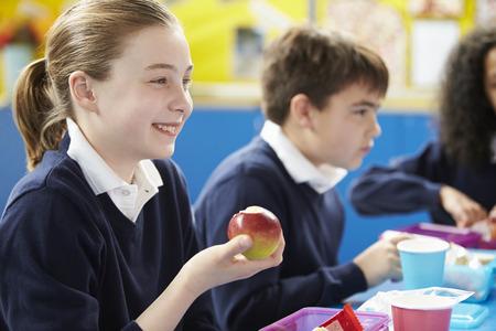 uniforme escolar: Los escolares sentado en la mesa Comer Almuerzo en lonchera