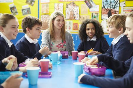 Los escolares con el maestro sentado en la mesa de comer el almuerzo Foto de archivo