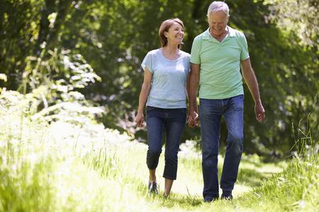 tercera edad: Pares mayores que recorren en campo del verano