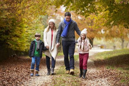 caminando: Familia que recorre lo largo de ruta de otoño